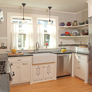 Small craftsman enclosed kitchen appliance - Inspiration for a small craftsman u-shaped light wood floor and brown floor enclosed kitchen remodel in Minneapolis with a farmhouse sink, white cabinets, stainless steel appliances, recessed-panel cabinets, white backsplash, subway tile backsplash, no island and soapstone countertops