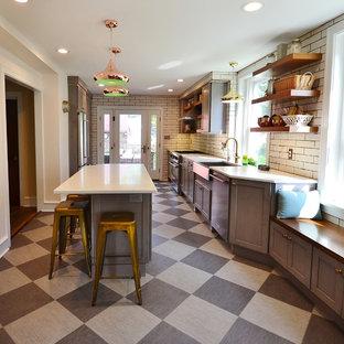 フィラデルフィアの中サイズのトランジショナルスタイルのおしゃれなキッチン (エプロンフロントシンク、フラットパネル扉のキャビネット、グレーのキャビネット、クオーツストーンカウンター、白いキッチンパネル、サブウェイタイルのキッチンパネル、シルバーの調理設備の、クッションフロア、マルチカラーの床、白いキッチンカウンター) の写真