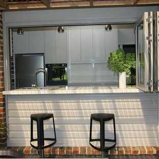 Large modern kitchen pantry photos - Inspiration for a large modern galley slate floor kitchen pantry remodel in Sydney with an undermount sink, flat-panel cabinets, white cabinets, quartz countertops, brown backsplash, glass sheet backsplash, stainless steel appliances and no island