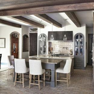 На фото: кухни в классическом стиле с коричневыми фасадами, обеденным столом, кирпичным полом и островом