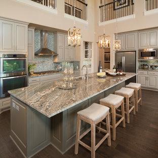 Zweizeilige Klassische Küche mit Unterbauwaschbecken, profilierten Schrankfronten, grauen Schränken, Küchenrückwand in Blau, Rückwand aus Mosaikfliesen, Küchengeräten aus Edelstahl, dunklem Holzboden, Kücheninsel und grauer Arbeitsplatte in Austin