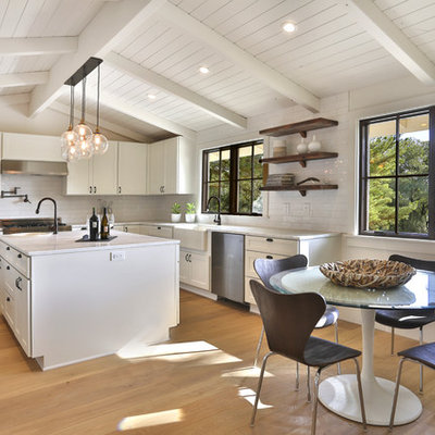 Inspiration for a mid-sized farmhouse u-shaped light wood floor and brown floor eat-in kitchen remodel in San Francisco with an island, a farmhouse sink, raised-panel cabinets, white cabinets, granite countertops, white backsplash, subway tile backsplash and stainless steel appliances