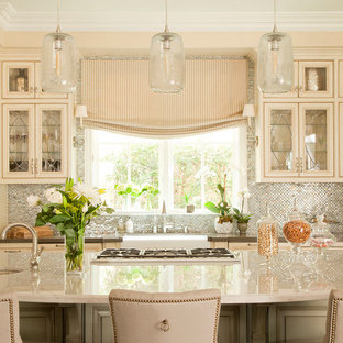 Elegant kitchen photo in Los Angeles with a farmhouse sink, beaded inset cabinets, beige cabinets, metallic backsplash, mosaic tile backsplash, stainless steel appliances and beige countertops
