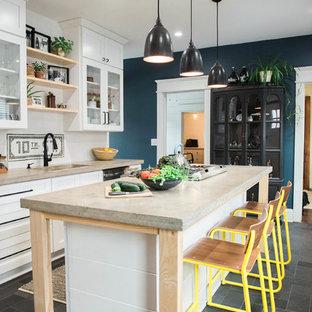 Réalisation d'une petite cuisine linéaire champêtre avec un évier encastré, des portes de placard blanches, un plan de travail en béton, une crédence blanche, une crédence en carreau de céramique, un électroménager en acier inoxydable, un sol en ardoise, un îlot central, un sol gris, un placard à porte shaker et un plan de travail gris.