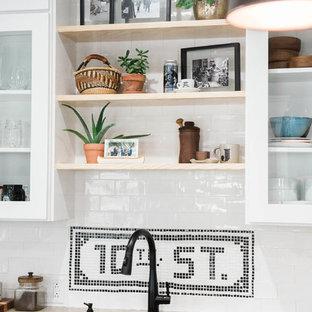 ニューヨークの小さいエクレクティックスタイルのおしゃれなキッチン (アンダーカウンターシンク、ガラス扉のキャビネット、白いキャビネット、コンクリートカウンター、白いキッチンパネル、セラミックタイルのキッチンパネル、シルバーの調理設備の、スレートの床、グレーの床) の写真