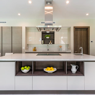 Large contemporary open concept kitchen designs - Example of a large trendy l-shaped porcelain tile and gray floor open concept kitchen design in Miami with a double-bowl sink, flat-panel cabinets, gray cabinets, quartz countertops, paneled appliances, an island, white countertops, white backsplash and stone slab backsplash