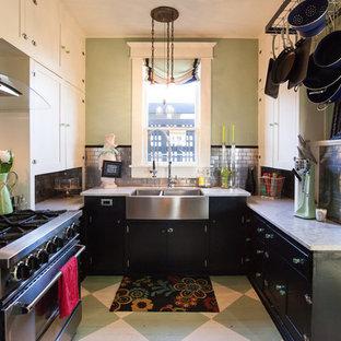 Inredning av ett industriellt avskilt, litet grå grått u-kök, med en rustik diskho, skåp i shakerstil, svarta skåp, marmorbänkskiva, stänkskydd med metallisk yta, rostfria vitvaror, målat trägolv, stänkskydd i tunnelbanekakel och grönt golv