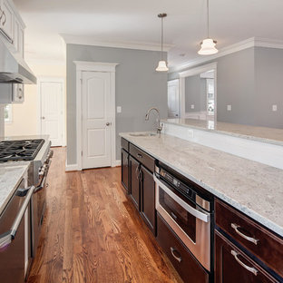 Kitchen - transitional l-shaped medium tone wood floor kitchen idea in DC Metro with an undermount sink, white cabinets, granite countertops, stainless steel appliances and an island
