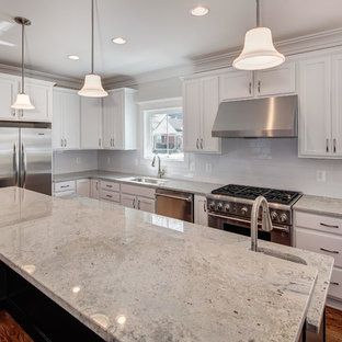 Example of a transitional l-shaped medium tone wood floor kitchen design in DC Metro with an undermount sink, white cabinets, granite countertops, stainless steel appliances and an island