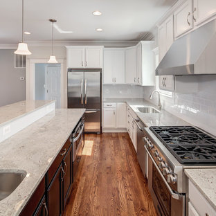 Transitional l-shaped medium tone wood floor kitchen photo in DC Metro with an undermount sink, white cabinets, granite countertops, stainless steel appliances and an island