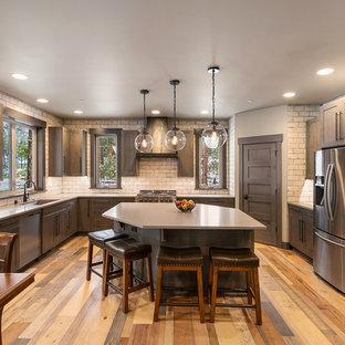 Foto di una cucina stile rurale con lavello sottopiano, ante in stile shaker, ante marroni, paraspruzzi bianco, paraspruzzi con piastrelle diamantate, elettrodomestici in acciaio inossidabile, pavimento in legno massello medio, isola, pavimento marrone e top beige
