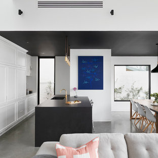 Photo of a contemporary galley open plan kitchen in Melbourne with recessed-panel cabinets, white cabinets, concrete floors and a peninsula.