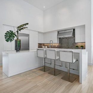 Large contemporary open concept kitchen photos - Example of a large trendy l-shaped beige floor open concept kitchen design in Miami with flat-panel cabinets, white cabinets, gray backsplash, stainless steel appliances, two islands and white countertops
