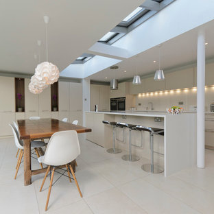Design ideas for a contemporary galley eat-in kitchen in Other with flat-panel cabinets, beige cabinets and white floor.