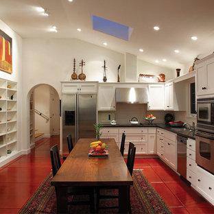 Mediterrane Küche in L-Form mit Schrankfronten im Shaker-Stil, weißen Schränken, Küchengeräten aus Edelstahl und rotem Boden in Los Angeles