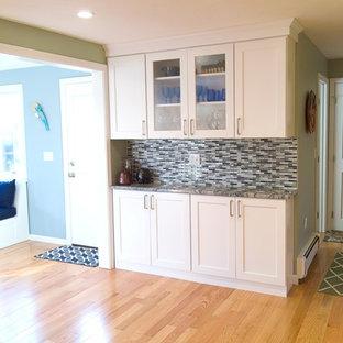 Große Moderne Wohnküche in L-Form mit Unterbauwaschbecken, Schrankfronten im Shaker-Stil, gelben Schränken, Quarzit-Arbeitsplatte, Glasrückwand, Küchengeräten aus Edelstahl, braunem Holzboden und Kücheninsel in Boston