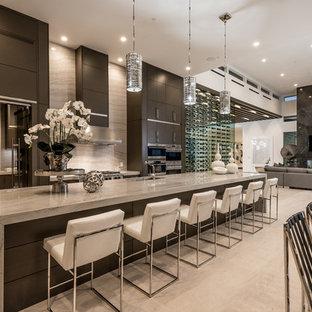 ラスベガスの広いコンテンポラリースタイルのおしゃれなキッチン (アンダーカウンターシンク、フラットパネル扉のキャビネット、濃色木目調キャビネット、シルバーの調理設備、ベージュの床、御影石カウンター、グレーのキッチンパネル、石スラブのキッチンパネル、ライムストーンの床、ベージュのキッチンカウンター) の写真