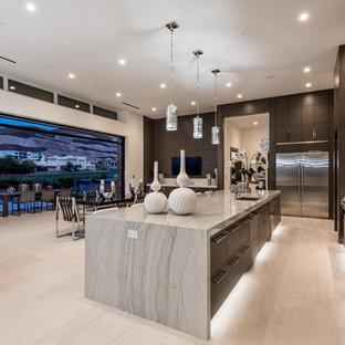 Inredning av ett modernt stort beige beige kök, med en undermonterad diskho, släta luckor, skåp i mörkt trä, granitbänkskiva, grått stänkskydd, stänkskydd i sten, rostfria vitvaror, kalkstensgolv, en köksö och beiget golv