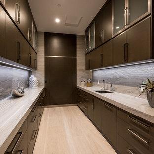 Immagine di una grande cucina minimal con lavello sottopiano, ante lisce, ante in legno bruno, top in granito, paraspruzzi grigio, paraspruzzi in lastra di pietra, elettrodomestici in acciaio inossidabile, pavimento in pietra calcarea, isola, pavimento beige e top beige