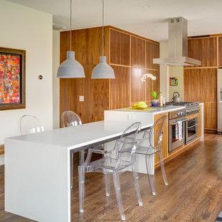 カンザスシティのコンテンポラリースタイルのおしゃれなアイランドキッチン (アンダーカウンターシンク、フラットパネル扉のキャビネット、中間色木目調キャビネット、シルバーの調理設備の、無垢フローリング、人工大理石カウンター) の写真