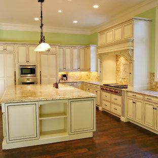チャールストンの巨大な地中海スタイルのおしゃれなキッチン (一体型シンク、レイズドパネル扉のキャビネット、ベージュのキャビネット、御影石カウンター、茶色いキッチンパネル、磁器タイルのキッチンパネル、シルバーの調理設備の、濃色無垢フローリング) の写真