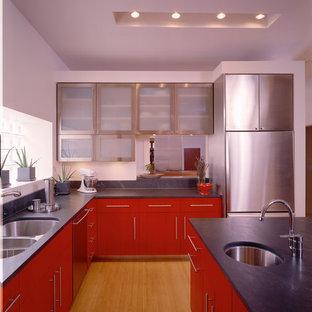 Offene, Mittelgroße Moderne Küche in L-Form mit roten Schränken, Doppelwaschbecken, flächenbündigen Schrankfronten, Küchengeräten aus Edelstahl, Küchenrückwand in Grau, Bambusparkett, Kücheninsel und beigem Boden in Chicago