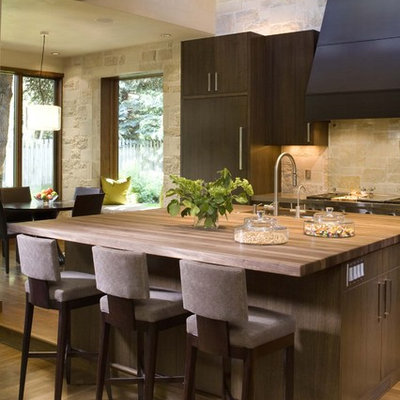 Mountain style kitchen photo in Denver with wood countertops and limestone backsplash