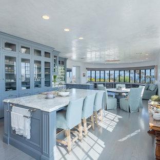 Inspiration pour une cuisine marine avec un plan de travail en marbre, un évier de ferme, un placard avec porte à panneau surélevé et un îlot central.