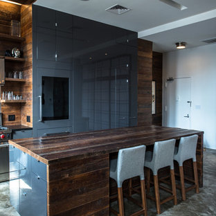 Mid-sized industrial eat-in kitchen ideas - Example of a mid-sized urban l-shaped concrete floor and gray floor eat-in kitchen design in New York with flat-panel cabinets, gray cabinets, wood countertops, brown backsplash, wood backsplash, stainless steel appliances and an island