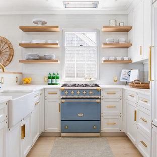 ボストンのビーチスタイルのおしゃれなコの字型キッチン (エプロンフロントシンク、落し込みパネル扉のキャビネット、白いキャビネット、白いキッチンパネル、サブウェイタイルのキッチンパネル、カラー調理設備、淡色無垢フローリング、アイランドなし) の写真