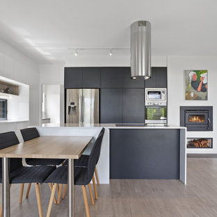 This is an example of a contemporary l-shaped eat-in kitchen in Sunshine Coast with a double-bowl sink, flat-panel cabinets, black cabinets, stainless steel appliances, light hardwood floors, an island, beige floor and white benchtop.