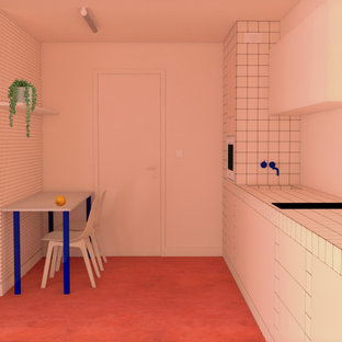 Design ideas for a small single-wall open plan kitchen in Other with a drop-in sink, flat-panel cabinets, tile benchtops, panelled appliances, concrete floors, no island, pink floor and pink benchtop.