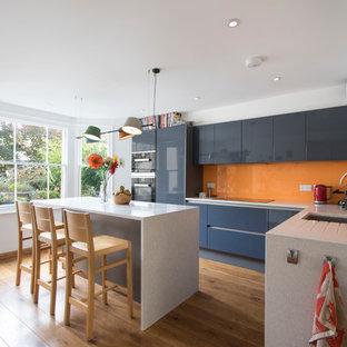 Moderne Küche in L-Form mit Unterbauwaschbecken, flächenbündigen Schrankfronten, blauen Schränken, Küchenrückwand in Orange, Glasrückwand, schwarzen Elektrogeräten, braunem Holzboden, Kücheninsel und weißer Arbeitsplatte in Sonstige