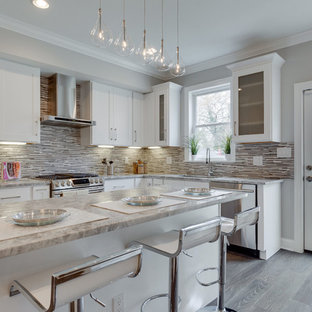 Mid-sized transitional kitchen pictures - Mid-sized transitional l-shaped medium tone wood floor and brown floor kitchen photo in New York with an undermount sink, shaker cabinets, white cabinets, multicolored backsplash, mosaic tile backsplash, stainless steel appliances and an island