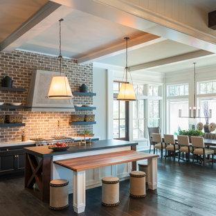 Offene, Große Landhausstil Küche in L-Form mit Einbauwaschbecken, Schrankfronten mit vertiefter Füllung, weißen Schränken, Küchengeräten aus Edelstahl, dunklem Holzboden, Kücheninsel, Rückwand aus Backstein, Mineralwerkstoff-Arbeitsplatte und Küchenrückwand in Rot in Charleston