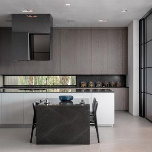 Diseño de cocina minimalista, grande, con armarios con paneles lisos, puertas de armario marrones, encimera de acrílico, electrodomésticos con paneles, suelo de cemento, una isla, suelo gris y encimeras negras