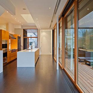Foto de cocina de galera, actual, con electrodomésticos de acero inoxidable, armarios con paneles lisos y puertas de armario de madera oscura