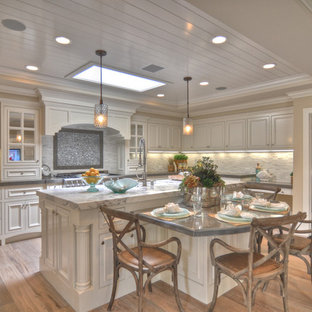 Coastal kitchen designs - Inspiration for a coastal kitchen remodel in Los Angeles with recessed-panel cabinets, white cabinets and beige backsplash