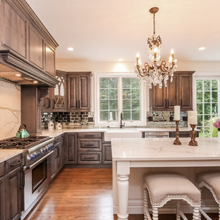 Mid-sized traditional kitchen ideas - Kitchen - mid-sized traditional u-shaped medium tone wood floor kitchen idea in Other with a farmhouse sink, raised-panel cabinets, metallic backsplash, subway tile backsplash, stainless steel appliances, an island, marble countertops and gray cabinets