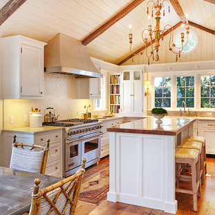 Inspiration for a country u-shaped eat-in kitchen in New York with an undermount sink, beaded inset cabinets, white cabinets, marble benchtops, white splashback, ceramic splashback, panelled appliances, with island and medium hardwood floors.