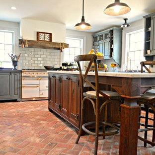フィラデルフィアの大きいカントリー風おしゃれなキッチン (エプロンフロントシンク、レイズドパネル扉のキャビネット、青いキャビネット、大理石カウンター、白いキッチンパネル、サブウェイタイルのキッチンパネル、パネルと同色の調理設備、レンガの床、赤い床、グレーのキッチンカウンター) の写真