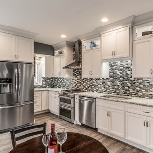 Small traditional kitchen pictures - Small elegant single-wall vinyl floor and brown floor kitchen photo in Philadelphia with a drop-in sink, flat-panel cabinets, white cabinets, granite countertops, multicolored backsplash, ceramic backsplash, stainless steel appliances, no island and gray countertops