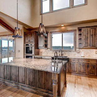 This is an example of a large country u-shaped kitchen in Denver with a farmhouse sink, raised-panel cabinets, dark wood cabinets, granite benchtops, beige splashback, stone tile splashback, stainless steel appliances, light hardwood floors, with island, brown floor and multi-coloured benchtop.
