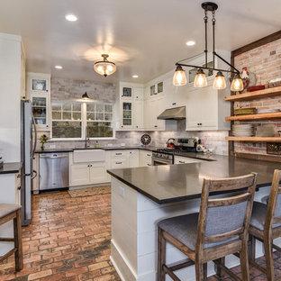 Lantlig inredning av ett stort u-kök, med en rustik diskho, skåp i shakerstil, vita skåp, stänkskydd i tegel, rostfria vitvaror, tegelgolv, en halv köksö, rött golv och beige stänkskydd