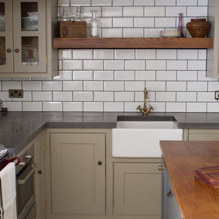 Small traditional l-shaped separate kitchen in Gloucestershire with a farmhouse sink, grey cabinets, concrete benchtops, white splashback, subway tile splashback, stainless steel appliances, limestone floors, with island and beaded inset cabinets.