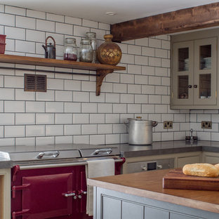 Small farmhouse enclosed kitchen remodeling - Inspiration for a small farmhouse l-shaped enclosed kitchen remodel in Gloucestershire with a farmhouse sink, gray cabinets, white backsplash, subway tile backsplash, an island, beaded inset cabinets and colored appliances