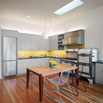 Example of a large trendy u-shaped eat-in kitchen design in San Francisco with white appliances, yellow backsplash, flat-panel cabinets, gray cabinets, mosaic tile backsplash, an undermount sink and no island