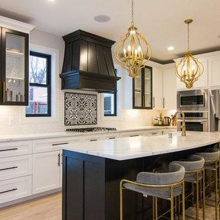 ミネアポリスの中くらいの地中海スタイルのおしゃれなキッチン (エプロンフロントシンク、ガラス扉のキャビネット、黒いキャビネット、白いキッチンパネル、サブウェイタイルのキッチンパネル、シルバーの調理設備、淡色無垢フローリング、ベージュの床、白いキッチンカウンター、クオーツストーンカウンター) の写真