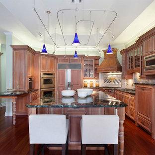 マイアミの中くらいの地中海スタイルのおしゃれなキッチン (アンダーカウンターシンク、レイズドパネル扉のキャビネット、中間色木目調キャビネット、オニキスカウンター、白いキッチンパネル、セラミックタイルのキッチンパネル、シルバーの調理設備、無垢フローリング、赤い床、黒いキッチンカウンター) の写真