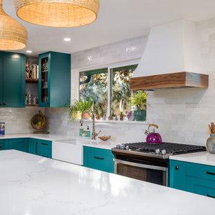 Exempel på ett mellanstort shabby chic-inspirerat vit vitt kök, med en rustik diskho, skåp i shakerstil, turkosa skåp, bänkskiva i kvarts, vitt stänkskydd, stänkskydd i keramik, rostfria vitvaror, laminatgolv, en köksö och brunt golv